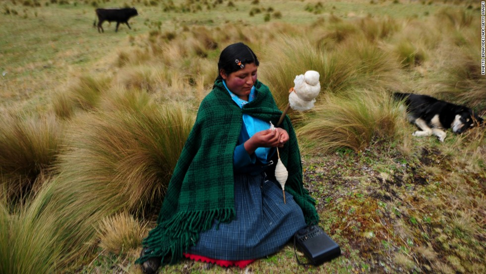 An Andean woman spins wool in front of the Perol lagoon at the Conga mine in Cajamarca.