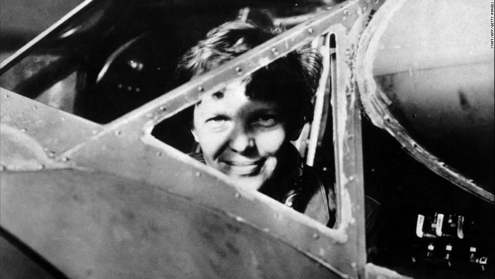 Earhart looks through the cockpit window of her plane.