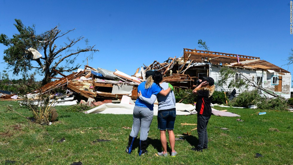 Kim Vanaken, left, consoles her sister Angela Coble, center, along with Amber Kelley while looking at what is left of Coble's house in El Reno on Saturday, June 1.