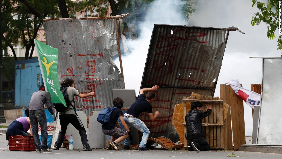 Demonstrators hide behind makeshift shields during clashes with Turkish riot police in Ankara on June 2.