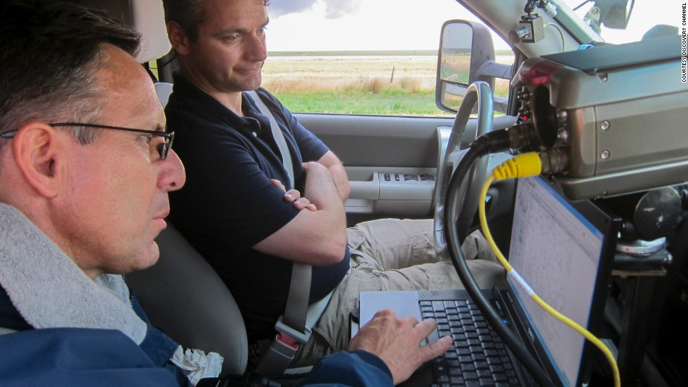 Tim Samaras and Carl Young read data. At a meteorological conference, Samaras encouraged Young to gather data from inside tornadoes for his thesis, and a partnership was born.