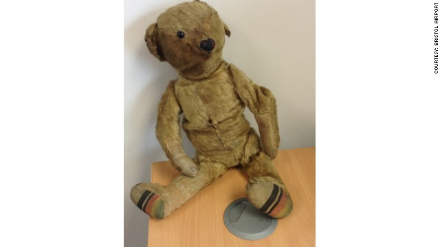 The bear and the old photograph were left in Bristol Airport's departure lounge more than 14 months ago.