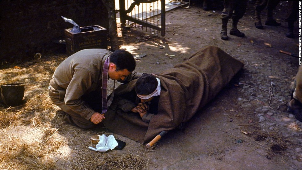 A U.S. Army chaplain kneels next to a wounded soldier to administer the eucharist and last rites, France, 1944.