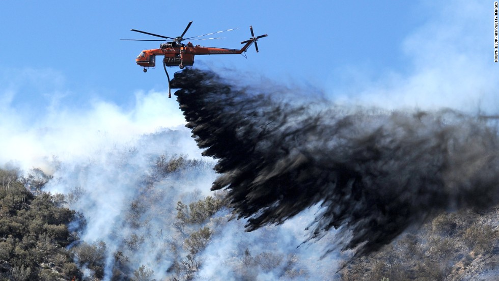A helicopter drops fire retardant on a flareup of the Powerhouse Fire near Lake Hughes, California, on Monday, June 3. More than 2,000 firefighters are battling the blaze, which started on May 30 and has spread to more than 30,000 acres about 70 miles north of Los Angeles.
