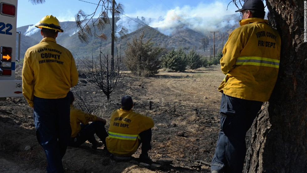 Firefighters watch a hillside burn near Lake Hughes on June 3.