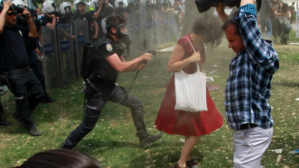 Completely turned, a police officer continues to spray her.