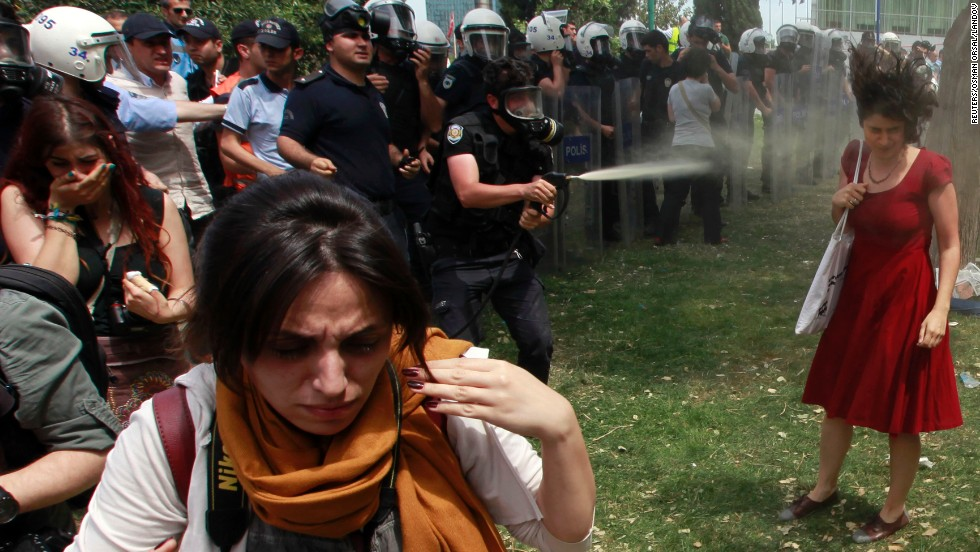 Police spray a woman in Taksim Square with what appears to be tear gas or pepper spray.