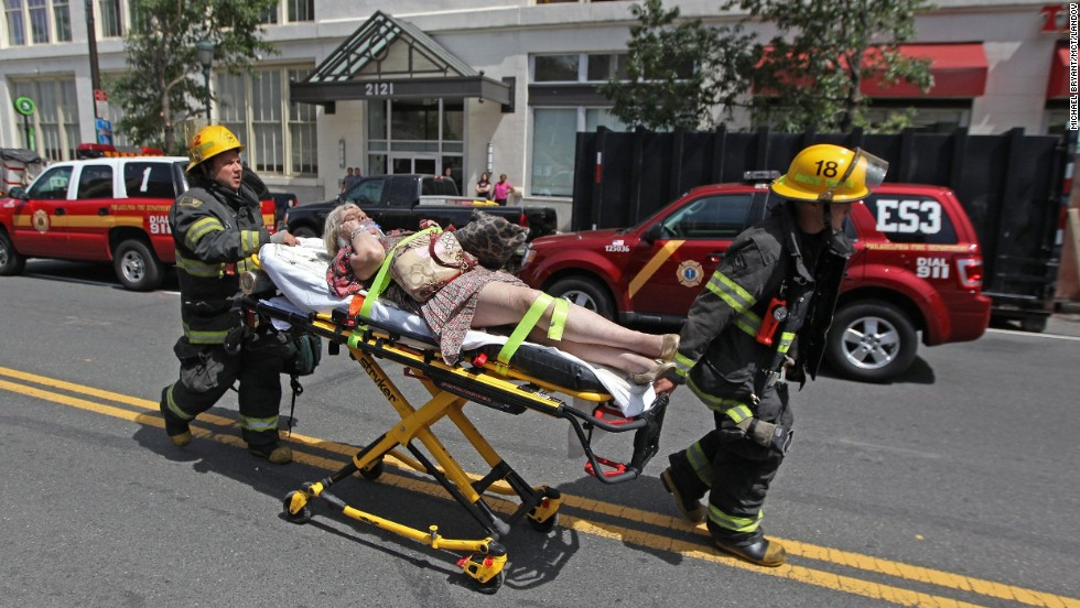 An injured woman is taken to an ambulance after the building collapse.