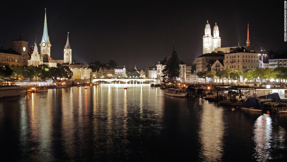 Zurich, Switzerland's largest city, rose two notches in the 2013 ECA survey to be the world's seventh most expensive city to live as an expat. In this photo, a night view of the old town of Zurich with the Grossmuenster church (R) right and left of the Limmat river.