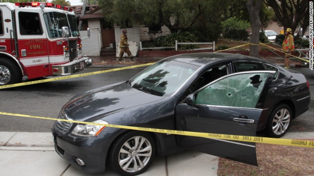 A car with windows shattered by bullets sits in front of a partially burned house where two bodies where found.  Authities believe that the incident may be related to the shootingon the compus of Santa Monica College.