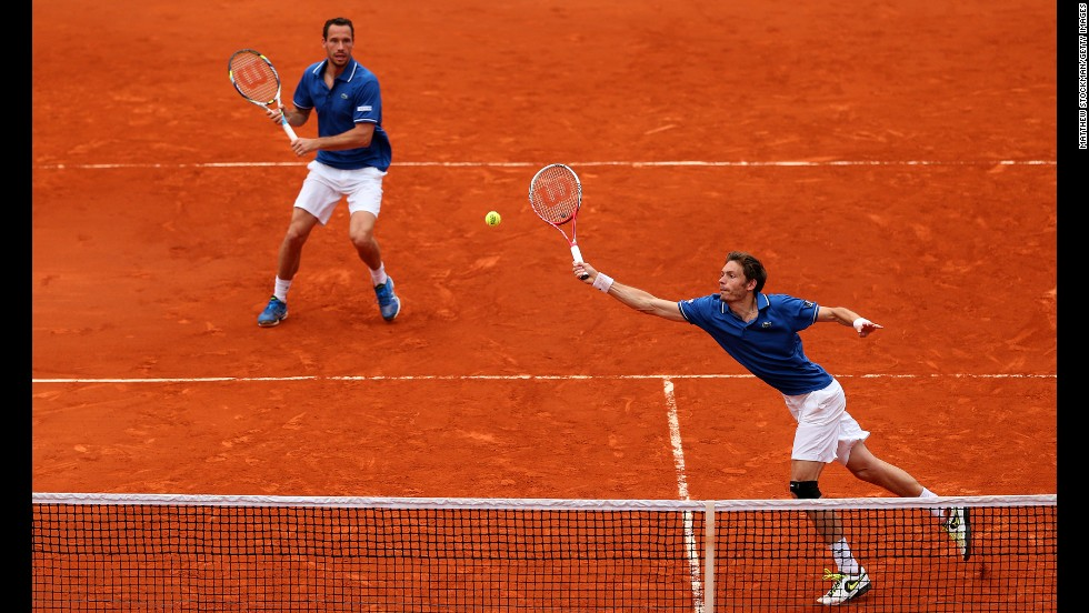 Mahut plays a forehand as his partner Llorda stands ready in the men's doubles final match.