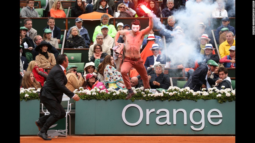 A protester runs onto the court with a lit flare during the match.