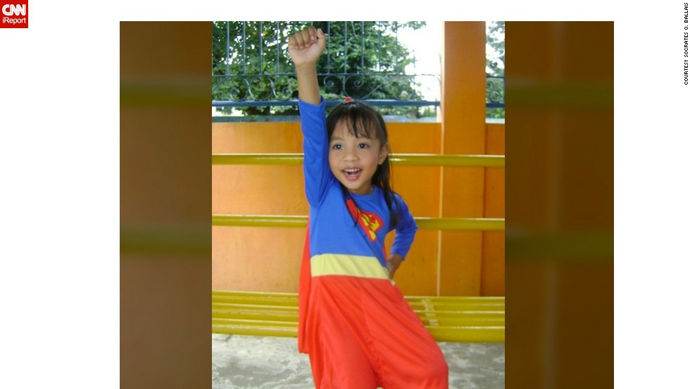 "<a href=""http://ireport.cnn.com/docs/DOC-979832"">Socrates Ballais</a> photographed his daughter, Iyah, dressed as ""Supergirl"" for a school presentation. Both he and his daughter are huge superhero fans.  When Iyah wears the Superman cape, she believes she really has superpowers. ""She has no fear of heights, and thinks she is as powerful as Superman. I keep on reminding her that acting like Supergirl is just like a pretend play. She does not believe it,"" he said. ""I had to make sure that I am around when she dons the Supergirl attire."""