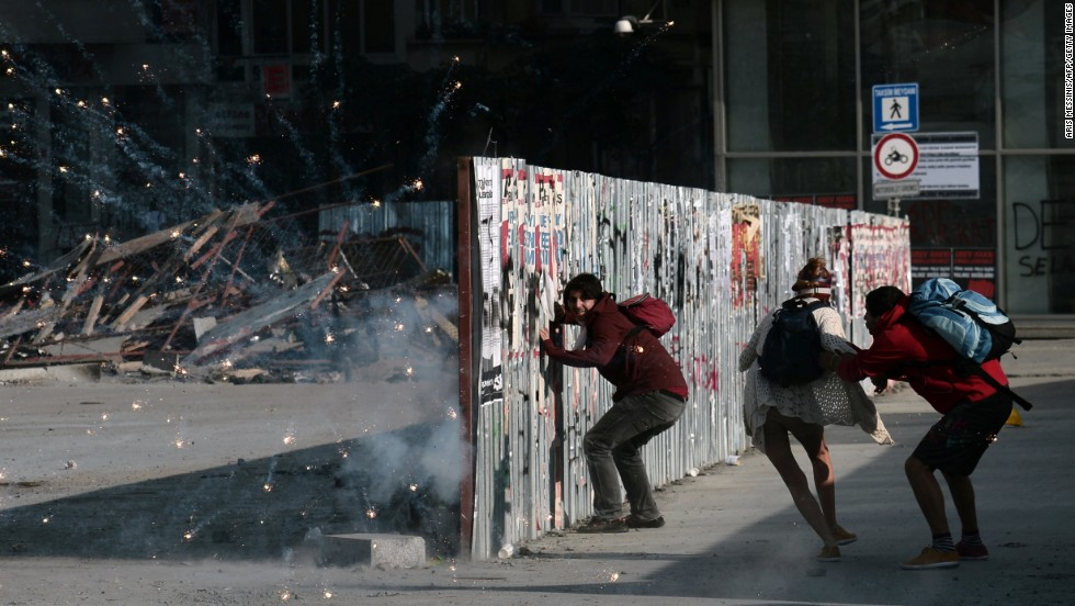Protesters take cover behind a barricade as fireworks go off nearby on June 11.