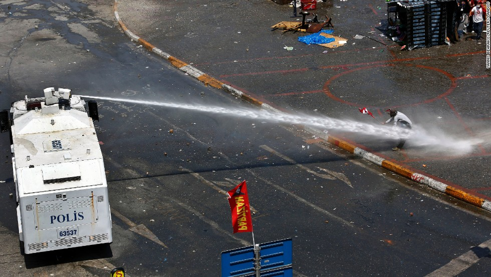 Riot police aim a water cannon at a protester as others take cover behind a makeshift shelter in Taksim Square on June 11.