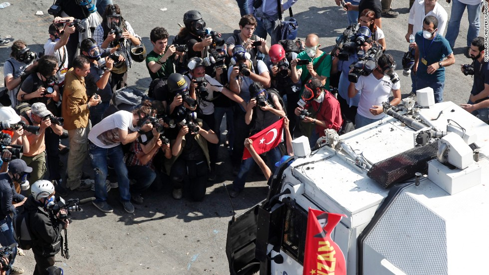 Photographers crowd around a protester posing in front of a riot police vehicle at Taksim Square on June 11.