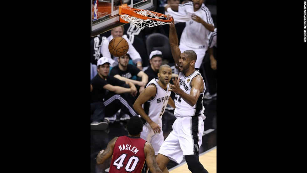 Tim Duncan of the San Antonio Spurs dunks the ball over Udonis Haslem of the Miami Heat.
