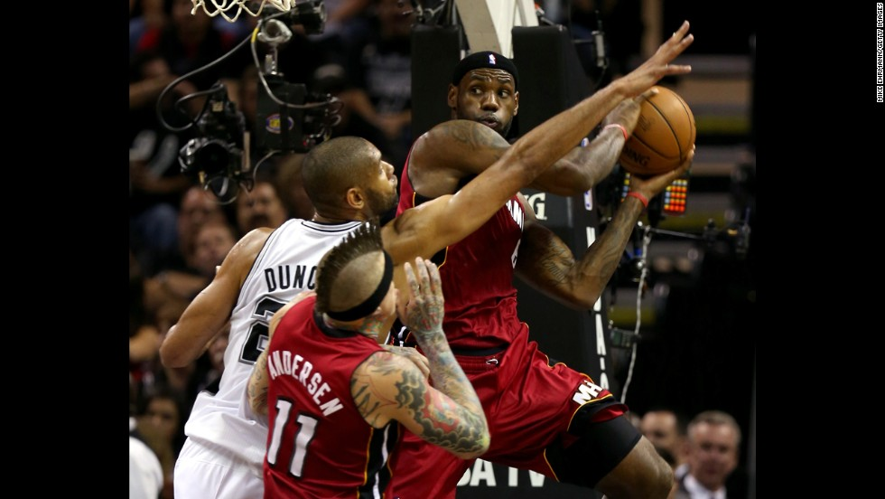 LeBron James of the Miami Heat looks to pass as he is guarded by Tim Duncan of the San Antonio Spurs.
