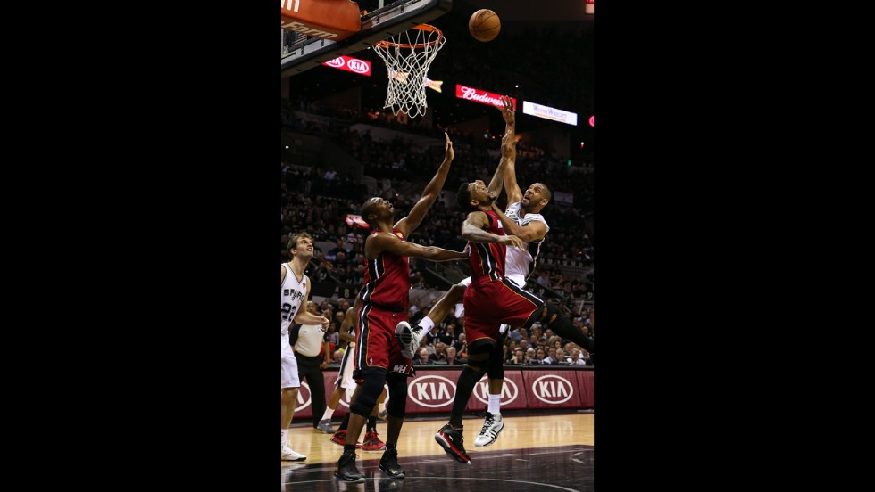 Tim Duncan of the San Antonio Spurs shoots over Udonis Haslem, center, and Chris Bosh, left, of the Miami Heat.