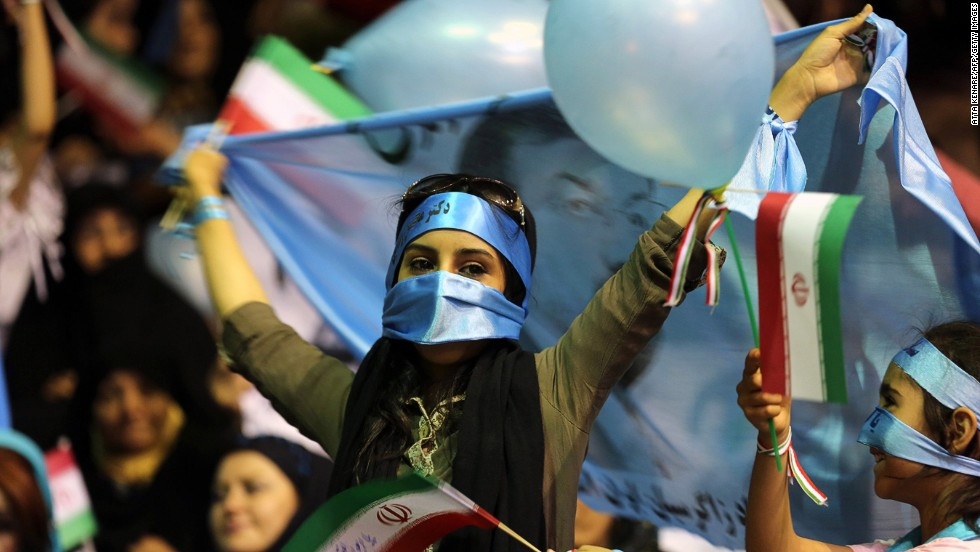 A supporter of Iranian presidential candidate Mohsen Rezaei, Iran's top commander during the war with Iraq, holds a blue flag bearing his portrait during a rally in Tehran on June 10.