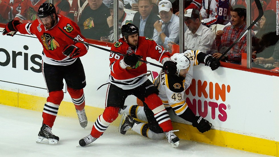Dave Bolland of the Chicago Blackhawks, center, checks Rich Peverley of the Boston Bruins into the boards.