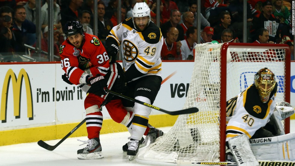 Dave Bolland of the Chicago Blackhawks passes the puck against Rich Peverley of the Boston Bruins.