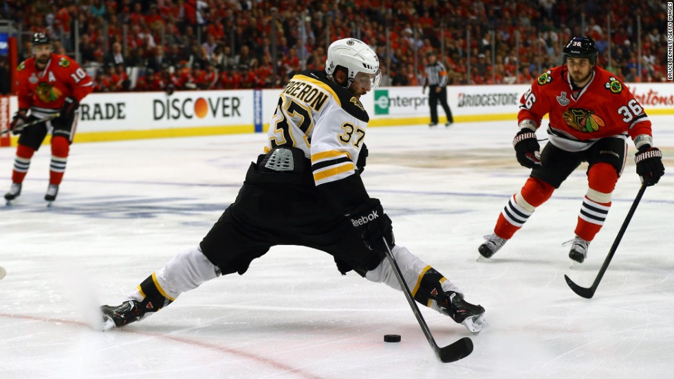 Patrice Bergeron of the Boston Bruins attempts to control the puck as Dave Bolland of the Chicago Blackhawks advances.