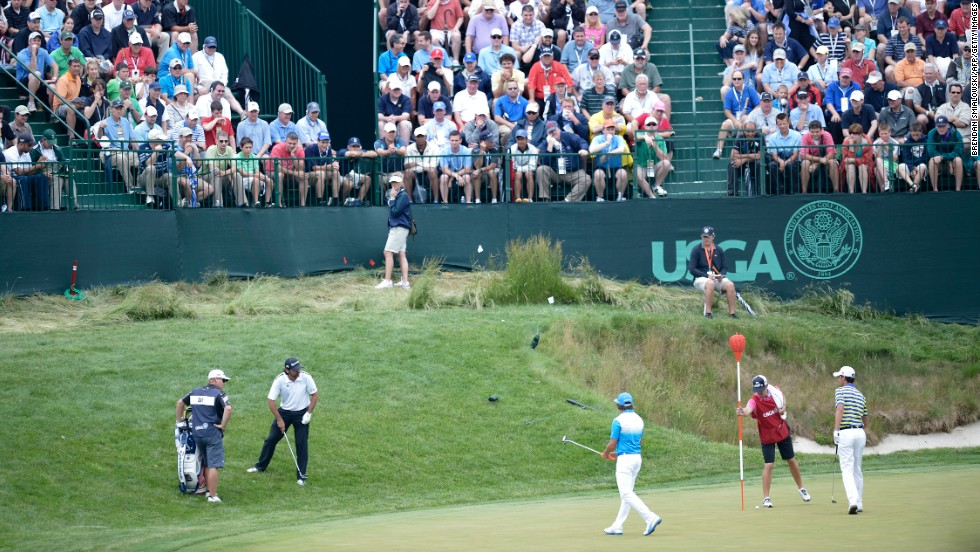 Jason Day of Australia, Rickie Fowler of the United States and Matteo Manassero of Italy play on the 17th green on June 13.