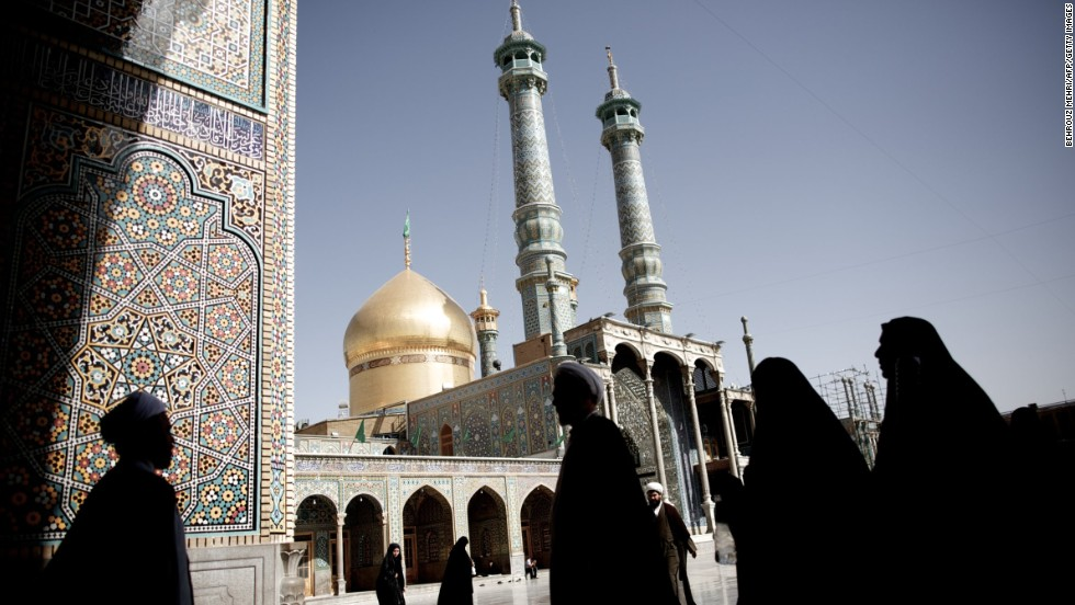 Pilgrims and clergymen walk across the courtyard of the Masoumeh holy shrine in the religious Shiite Muslim city of Qom on Sunday, June 9. Iran's powerful bazaar merchants and Shiite clergy spearheaded the 1979 Islamic revolution, but their role in the country's political scene has waned over the years, analysts say.