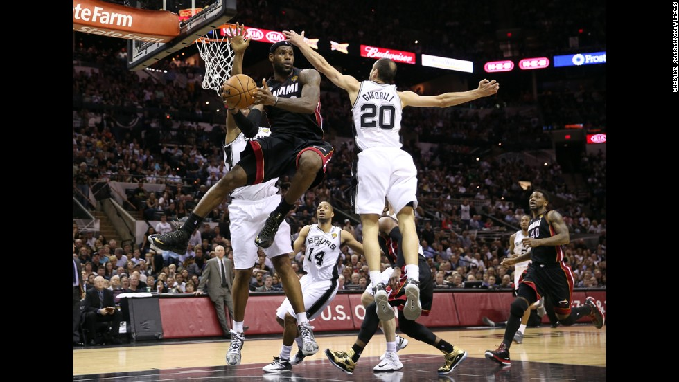LeBron James of the Miami Heat tries to pass around Manu Ginobili during the fourth quarter.