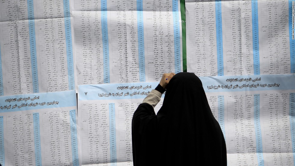 A woman checks out her ballot before voting in Iran's presidential elections at a Tehran polling station on June 14.