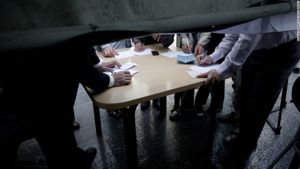 Voters fill out paper ballots in Tehran on June 14.