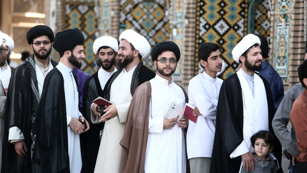 Iranian men wait to vote at a polling station at the Massoumeh shrine in the holy city of Qom, south of Tehran, during presidential elections on June 14.