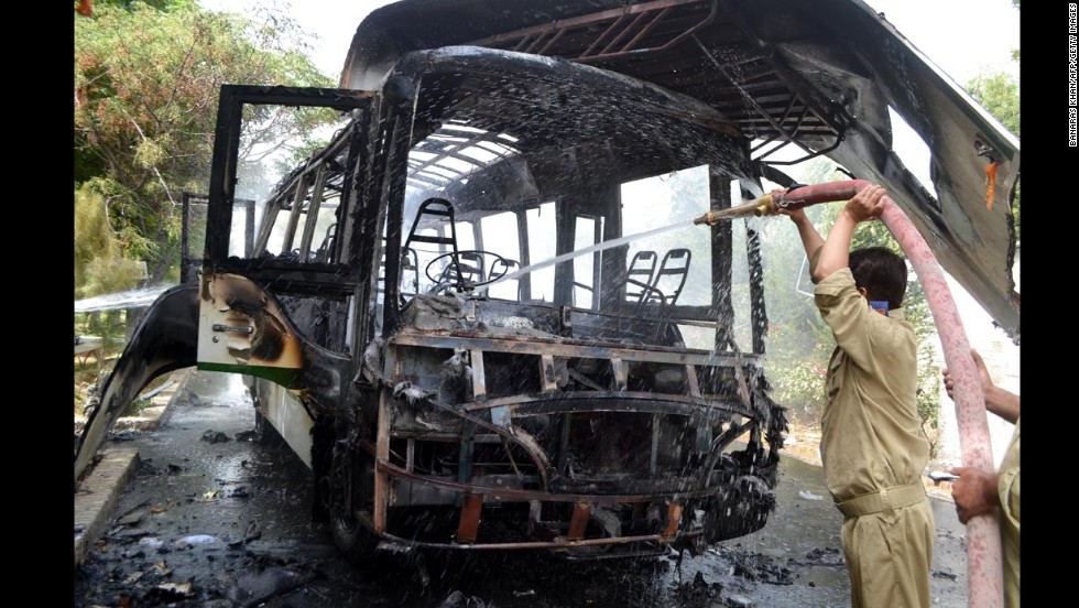 Firefighters extinguish a burning university bus after the bomb blast in Quetta.