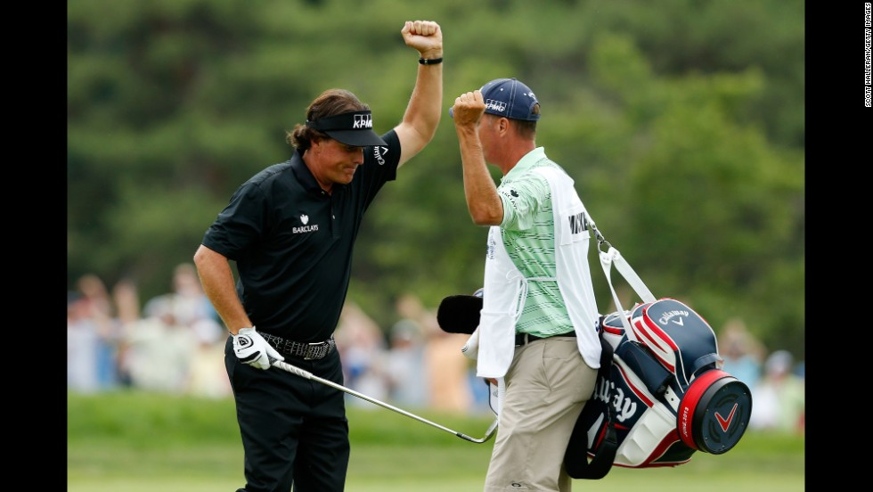 Phil Mickelson celebrates with caddie Jim Mackay after making a shot for eagle on the 10th hole par 4 during the final round on June 16.