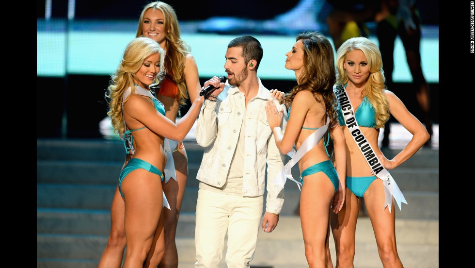Joe Jonas of the Jonas Brothers is surrounded by contestants while performing.