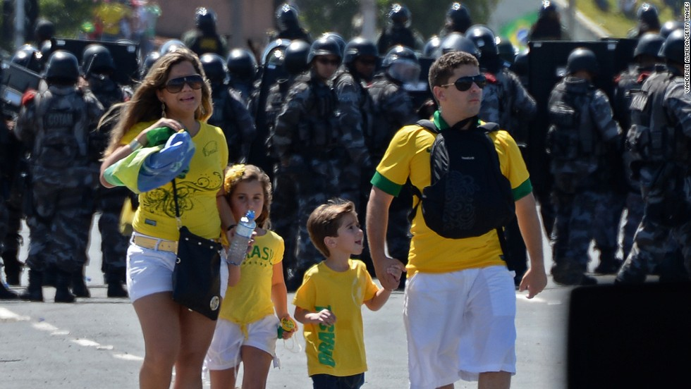 A family of four negotiate their way to the game as riot police prevent protesters from gaining access to Fortaleza's Castelao Stadium.