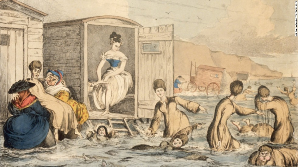 "In 1825, women wore ""bathing dresses"" at the beach. This illustration shows women of the era venturing into the ocean via bathing machines -- sort of a dressing room on wheels -- that brought them directly to the water."