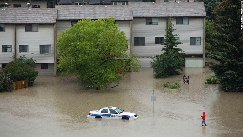 A woman walks toward an abandoned and partially submerged police car in Calgary's Sunnyside neighborhood on June 21.