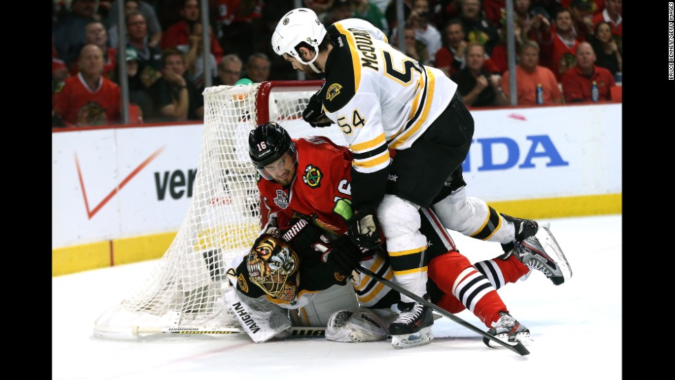 Marcus Kruger of Chicago trips over Boston's Tuukka Rask in the net.