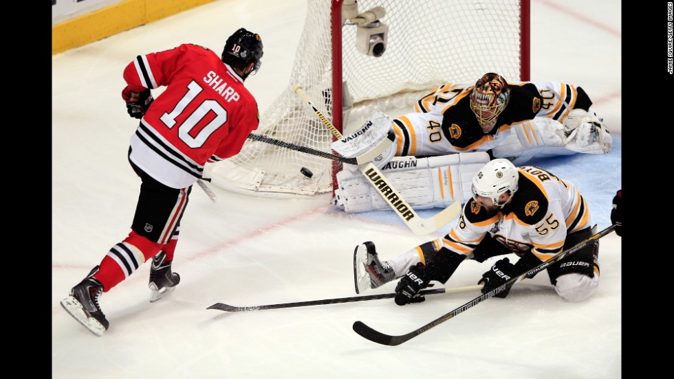 Patrick Sharp of the Chicago Blackhawks takes a shot against Tuukka Rask of the Boston Bruins.