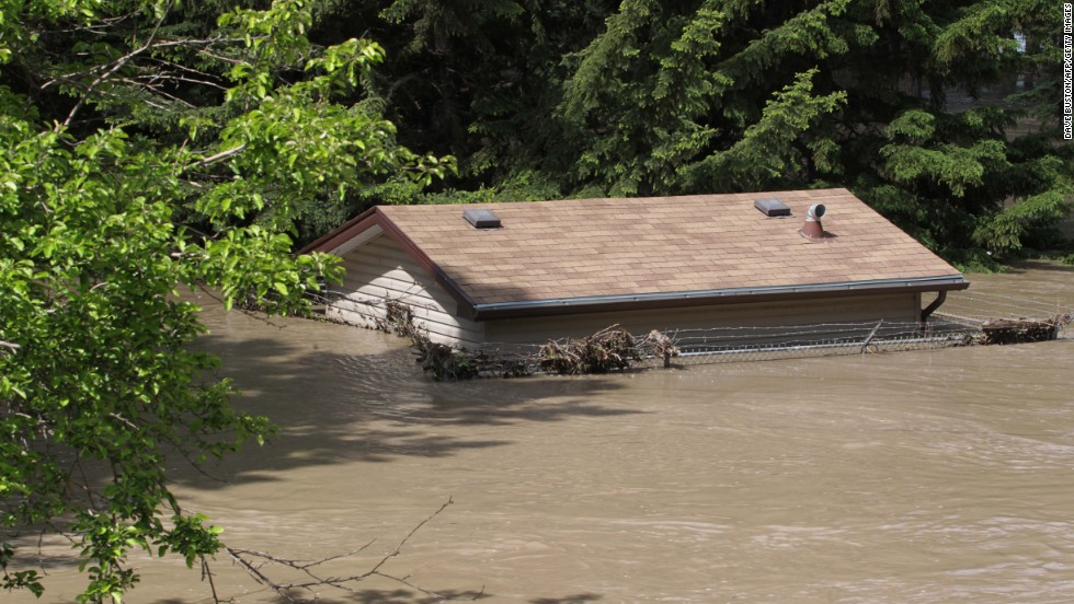 A house is submerged by floodwater at a park near the Bow River in Calgary on June 22.