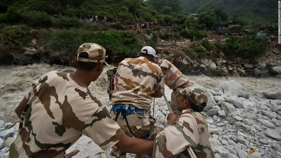 Police personnel use a rope rescue system to transport stranded pilgrims across a river in Govindghat on June 23.