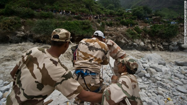 Indo-Tibetan Border Police (ITBP) personnel use a rope rescue system to transport stranded pilgrims across a river in Govind Ghat on June 23, 2013. Bad weather hampered rescue operations June 23 in northern India where up to 1,000 people are feared to have died in landslides and flash floods that have left pilgrims and tourists stranded without food or water.  AFP PHOTO/MANAN VATSYAYANA        (Photo credit should read MANAN VATSYAYANA/AFP/Getty Images)