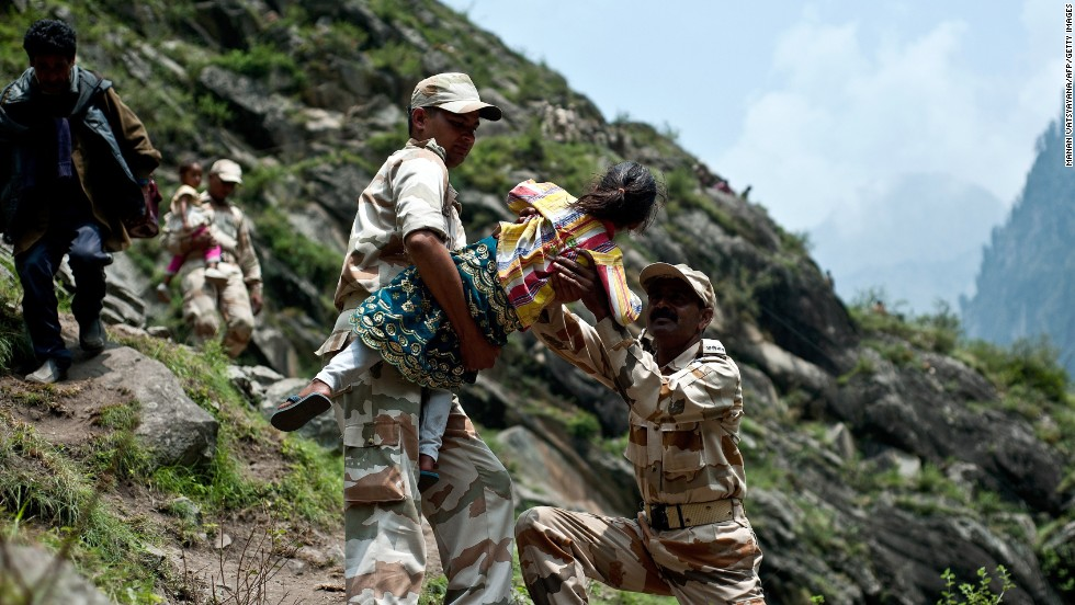 Police carry a child during efforts to help stranded Indian pilgrims on June 23 after a section of road was washed away in Govindghat.