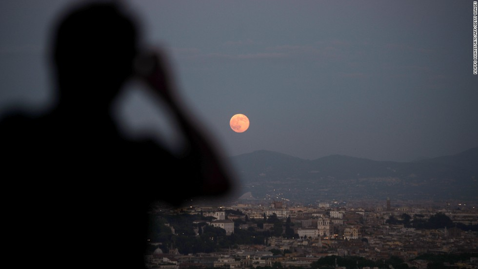 Onlookers view the full moon over the city of Rome on June 23.