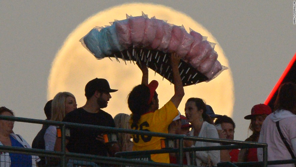A cotton candy vendor weaves through the crowd during the Los Angeles Angels' baseball game against the Pittsburgh Pirates on Saturday, June 22.