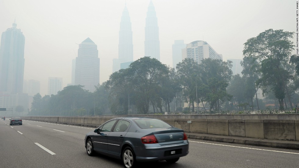 Motorists drive as haze shrouds Malaysia's landmark Petronas Twins Towers in Kuala Lumpur on June 23. The Malaysian government declared a state of emergency on June 23 in two southern areas.