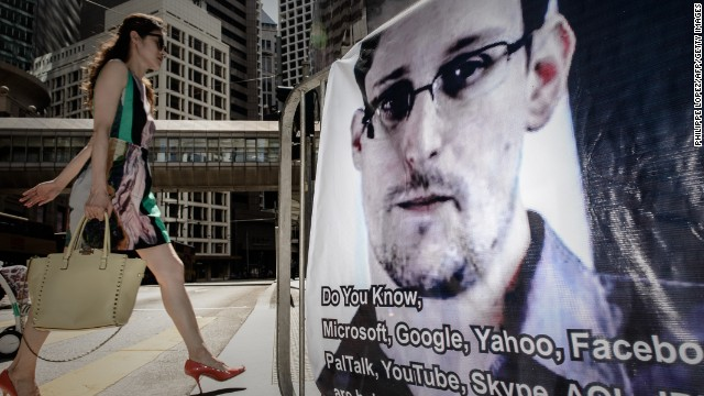 A woman walks past a banner displayed in support of former US spy Edward Snowden in Hong Kong on June 18, 2013.