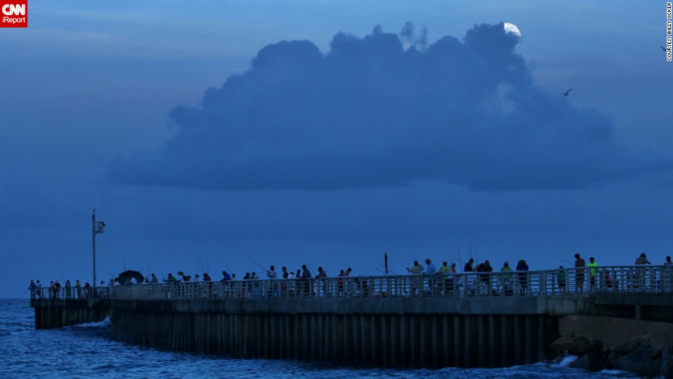 "<a href=""http://ireport.cnn.com/docs/DOC-993604"">Billy Ocker</a> stood on the pier of the Sebastian, Florida, inlet, photographing the supermoon peeking through the thick clouds overhead. ""The moon was late in its showing and I almost thought I might not be able to see it because of the clouds. But just when I was about to give up, the Sun went completely down and I could see the clouds starting to glow white and then the Supermoon,"" he said."